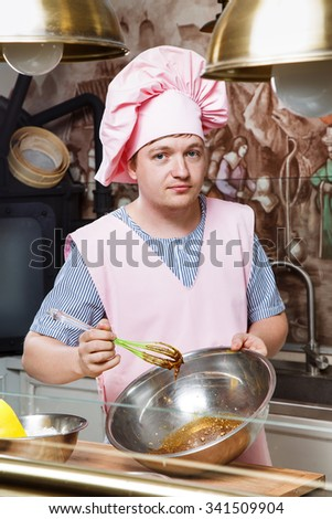 Young confectioner, wearing in pink apron, hat and striped shirt, holding green corolla, metallic bowl, and knead the dough for gingerbread, on the wooden board, in the kitchen with paintings