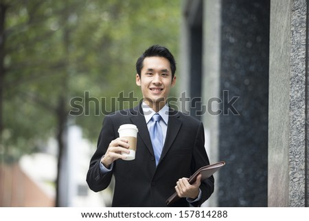 Young confident asian businessman walking in the city. - stock photo