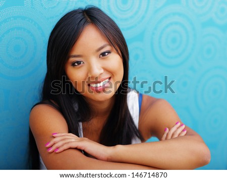 Young confident asian woman sitting on the floor at home - stock photo