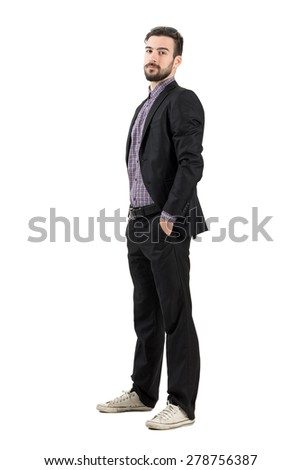Young confident bearded businessman in suit and sneakers looking at camera. Full body length portrait isolated over white studio background.
