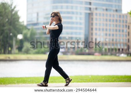 Young confident business woman walking at fast speed, looking at wristwatch, talking on cellphone on the city street in front of blue glass modern office building beside riverbank, full length - stock photo