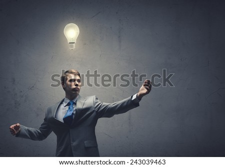 Young confident businessman and light bulb above his head