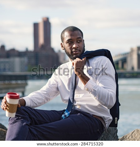 Young confident businessman portrait relaxing with a cup of coffee with Manhattan Bridge in the background. Brooklyn Dumbo Park, New York City. - stock photo