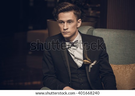 Young confident businessman sitting in armchair