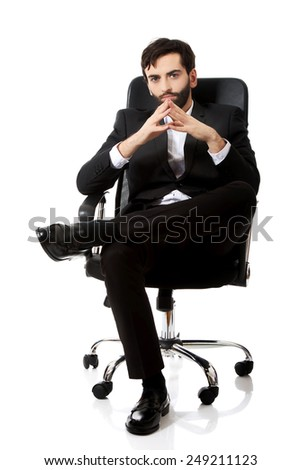 Young confident businessman sitting on a chair.