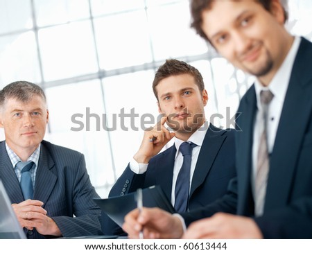 Young confident businessman sitting on the meeting at the office with colleagues.