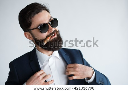 young confident businessman smoking a cigar and fixing his black suit with confidence on white background. Arrogant rich bearded man in sunglasses - stock photo
