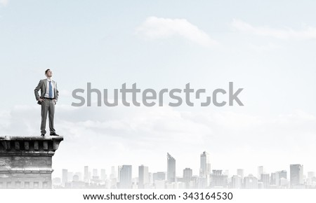 Young confident businessman standing on top of building