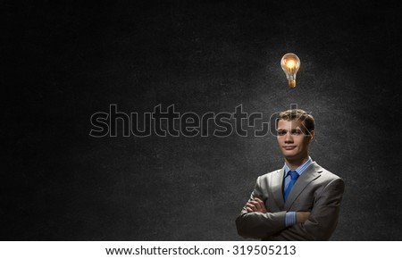 Young confident businessman with arms crossed on chest looking at light bulb