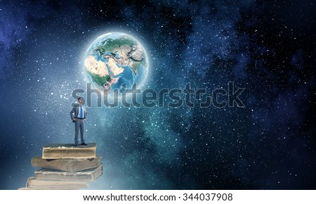 Young confident businessman with arms on waist standing on pile of old books. Elements of this image are furnished by NASA - stock photo