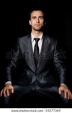 young confident businessman with hands on his knees