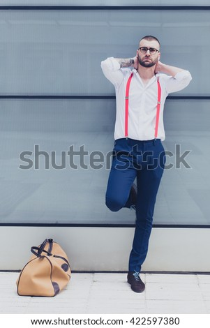 Young confident businessman with tattoos relaxing outdoors. Modern office background - stock photo