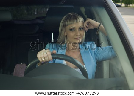 Young confident businesswoman driving car. City concept