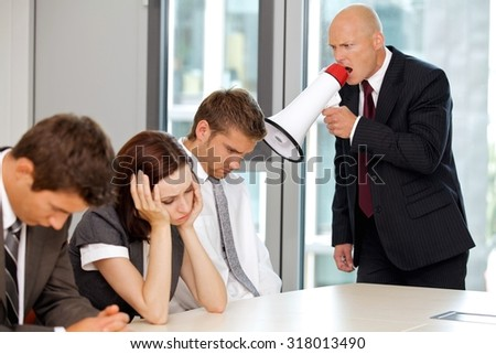 Young confident caucasian businessman screaming on his employee - stock photo