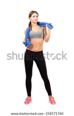 Young confident fitness female model posing with towel. Full body length portrait isolated over white background. - stock photo