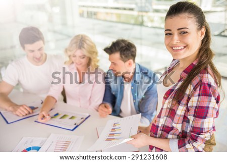 Young confident girl presenting new business concept to colleagues at meeting room.