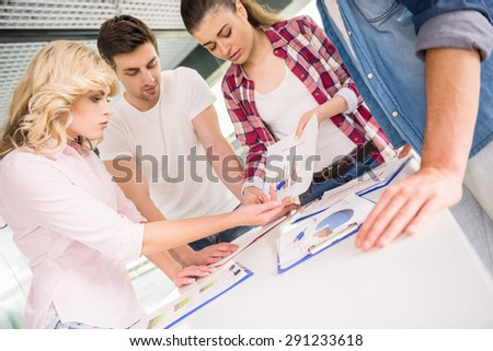 Young confident girl presenting new business concept to colleagues at meeting room. - stock photo