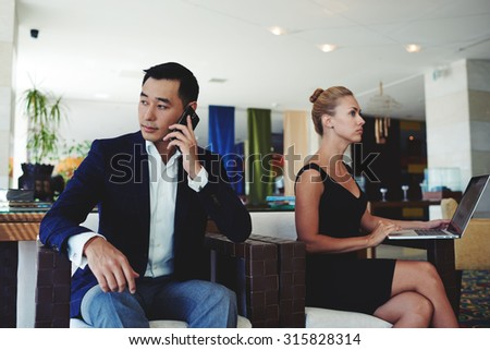 Young confident male manager calling with smart phone while sitting in office with female colleague,beautiful businesswoman working on laptop computer, successful man and woman preparing for meeting - stock photo