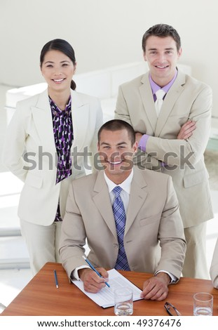 Young confident manager and his team smiling at the camera in the office