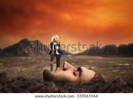 Young confident personal coach standing on the client's face in desert - stock photo