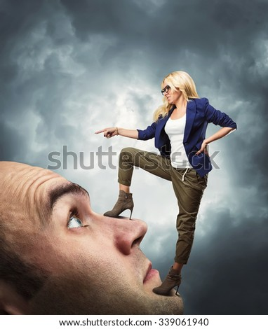 Young confident personal coach standing on the man's face - stock photo