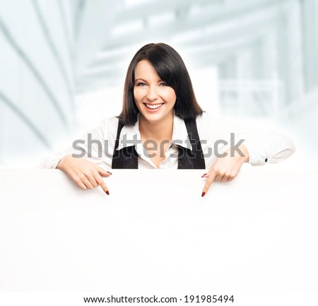 Young, confident, successful and beautiful business woman with a blank billboard over office background - stock photo