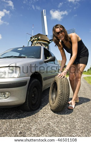 Young, confident woman, changing a flat tire on her car on a rural road with a wind mill in the background - stock photo