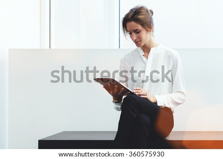 Young confident woman entrepreneur chatting on digital tablet with client while sitting on bench in office interior, intelligent female lawyer in formal wear reading electronic book during work break - stock photo