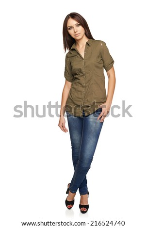 Young confident woman in jeans and green shirt standing relaxed in full length, over white studio background - stock photo