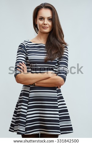 Young confident woman standing against gray background with crossed arms. Female model with long hair. - stock photo