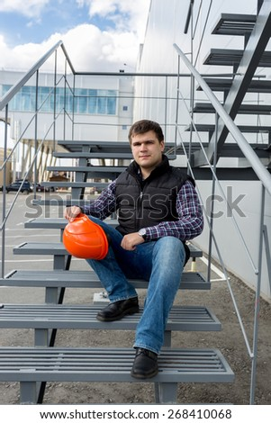 Young confident worker in hard hat sitting on metal staircase - stock photo