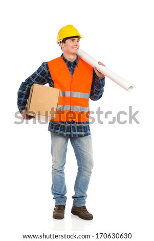 Young construction worker holds paper roll on his shoulder and carton box under his arm. Full length studio shot isolated on white.