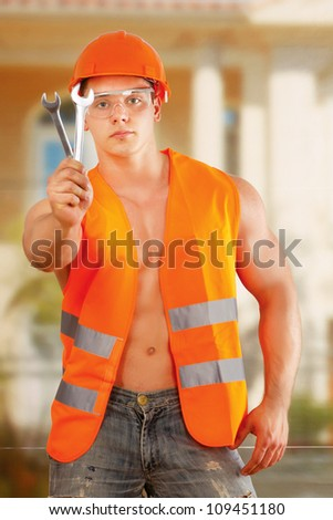 Young construction worker posing with spanner outdoors - stock photo