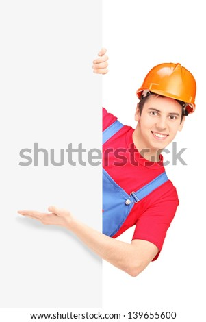 Young construction worker with helmet posing behind a blank panel isolated on white background - stock photo