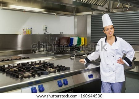 Young content chef standing next to hotplate in professional kitchen