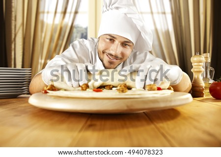young cook chef in kitchen with big window of sun light and wooden big table place of food