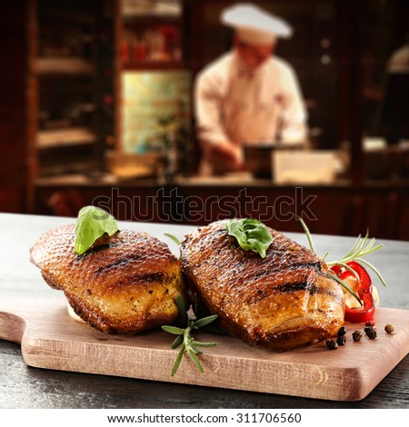 young cook in kitchen interior of bar and golden duck meat  - stock photo