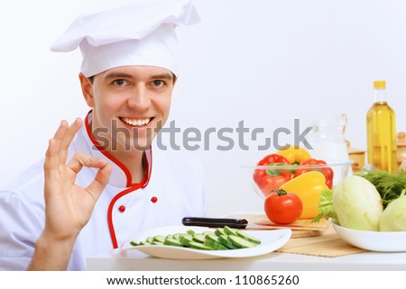 Young cook preparing food with red apron