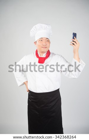Young Cook With Red Scarf Looking At Phone Surprised, Isolated - stock photo