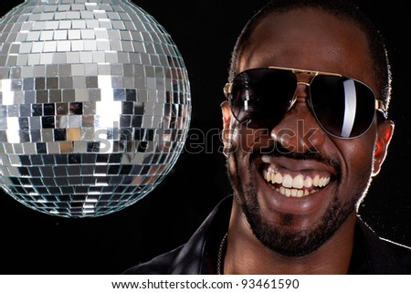 Young cool black man with disco ball over black background. - stock photo