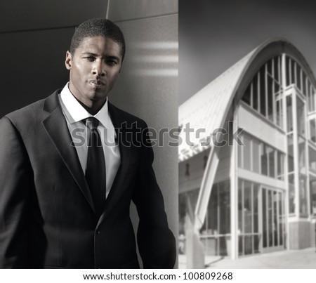 Young cool businessman in suit with dramatic lighting against modern wall with urban modern building in background - stock photo
