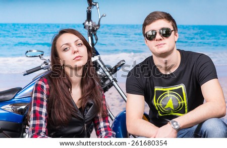 Young Cool Couple Looking Tough Crouching in front of Motorcycle on Beach - stock photo