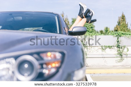 Young cool girl with shoes out of the automobile window to enjoy the view on a sport car