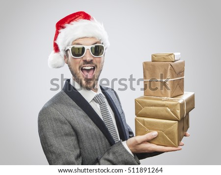 Young cool man with Santa Claus hat and sunglasses holding gifts