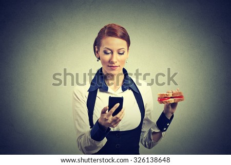 young corporate business woman reading news message on smart phone holding eating sandwich isolated on gray wall background. Human face expression. Social media app - stock photo