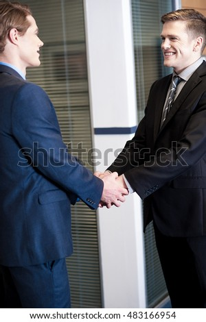 Young corporate executives shaking hands at office.