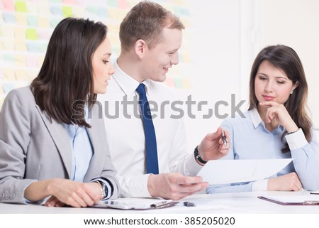 Young corporate worker and two elegant women in light interior