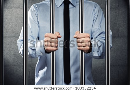 Young corrupted businessman in jail, behind the prison bars - stock photo