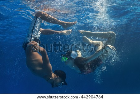 Young coule diving in swimming pool and have a fun at resort. - stock photo