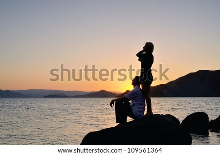 Young couple admiring the sunset on the beach - stock photo